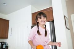 Girl in kitchen with a big smile holding an orange royalty free stock photography