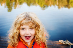 Happy girl out at the lake. Smiling little girl wearing a life jacket out on a dock at a lake Stock Photo