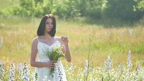 Happy girl outdoor in a field with flowers in nature. girl in a field smiling woman holding a bouquet of flowers stock footage