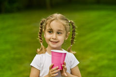 Happy girl outdoors. Portrait of happy girl with pigtails and pink cup outdoors, grass in background Royalty Free Stock Photo
