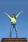 Happy girl outdoors. With outstretched arms, blue sky background Stock Image