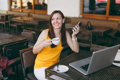 Happy girl in outdoors street coffee shop cafe sitting at table with laptop pc computer, texting message on mobile phone. Drink cup tea in restaurant during royalty free stock photography