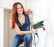 Happy girl in overalls with drill Royalty Free Stock Images