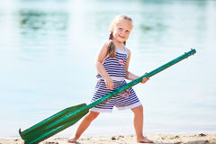 Happy girl with paddle at beach Royalty Free Stock Photo