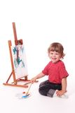 Happy girl painting on easel Stock Image