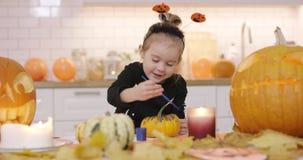Happy girl painting pumpkin stock footage