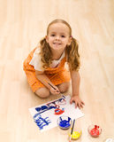Happy girl painting sitting on the floor Stock Images