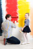 Happy girl painting wall with father Royalty Free Stock Photography
