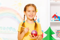 Happy girl paints New Year ball for Christmas tree. Happy girl painting New Year ball for Christmas tree while standing alone at the white table with decorations Stock Image
