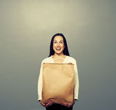 Happy girl with paper bag over dark Royalty Free Stock Photos