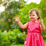 Happy girl at park with bubbles Stock Image