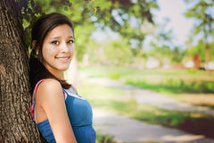 Happy girl in a park. Happy young woman  posing in a tree in a sunny summer day Stock Images