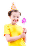 Happy girl in party hat holding colored candy. Stock Photos