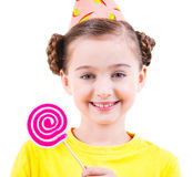 Happy girl in party hat holding colored candy. Stock Photo