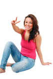 Happy girl peace sign. Smiling girl makes peace handsign, seated vertical pose with copy space Royalty Free Stock Photography
