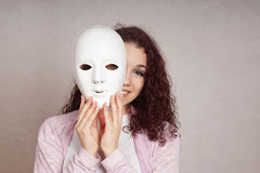 Happy girl peeking behind mask. Smiling young woman peeking from behind mask Royalty Free Stock Photography