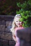 Happy girl peeks around stock images