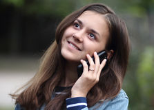 Happy girl with a phone. Happy and beautiful girl talking on the phone stock photography