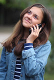 Happy girl with a phone. Happy and beautiful girl talking on the phone royalty free stock images