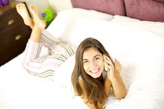 Happy girl on the phone in bed smiling and looking Stock Image