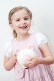 Happy girl with piggy bank Stock Photos