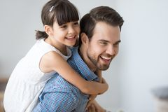 Happy girl piggyback young dad playing together. Excited playful young dad carry preschooler daughter on back, have fun playing at home together, smiling cute stock photos
