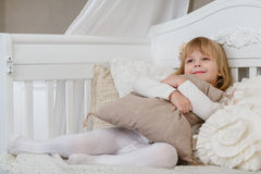 Happy girl with pillow. Royalty Free Stock Image