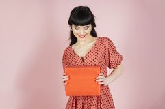 Happy girl on pink background. Woman receives present and smiles. Lady wears dotted dress and holds gift. Happiness, style, compliment, shopping, celebration royalty free stock images