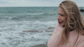 Happy girl in a pink coat near the sea during a. Happy loving girl in pink coat near the sea during a storm. strong wind stock footage