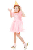 Happy  girl in a pink dress and hat dances Royalty Free Stock Photo