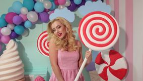 Girl having fun with big plastic candy in Studio. Happy girl in pink dress having fun with big plastic candy or Lollipop in the Studio. Barbie party. Candy girl stock video footage