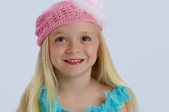 Happy girl in pink hat. Portrait of happy young blond girl wearing pink woollen hat; white studio background Stock Images