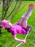 Happy girl in a pink hat having fun on a swing outdoor Royalty Free Stock Photos