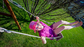 Happy girl in a pink hat having fun on a swing outdoor Royalty Free Stock Image