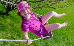 Happy girl in a pink hat having fun on a swing outdoor Stock Image