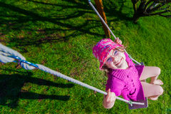 happy girl in a pink hat having fun on a swing outdoor Royalty Free Stock Photo