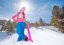 Happy girl in pink standing with sled. Smiling girl in cute pink outwear and warm hat standing on the slide with sled in the forest Stock Photography