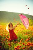 Happy girl with the pink umbrella over red poppy field royalty free stock photos
