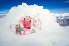 Happy girl in pink wear laying at the snow igloo Royalty Free Stock Photo