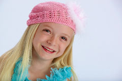 Happy girl in pink woollen hat. Happy young girl with long blond hair and pink woollen hat; studio background and copy space Royalty Free Stock Image