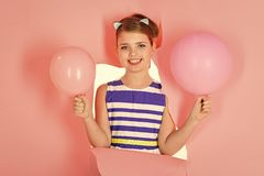 Happy girl play at home. Funny lovely child having fun in children room with balloons royalty free stock photography