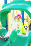 Happy girl play on slide playground in the park. Royalty Free Stock Photography