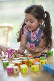 Happy girl playing with alphabet blocks at table Royalty Free Stock Photos