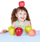 Happy girl playing with apples sitting at table Stock Images