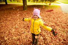 Happy girl playing with autumn leaves in park Royalty Free Stock Photo