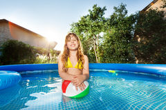 Happy girl playing with ball in swimming pool Stock Photo