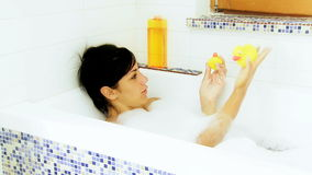 Happy girl playing in bath tub with ducks toy Royalty Free Stock Photography