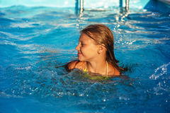Happy girl playing in blue water of swimming pool. Royalty Free Stock Images