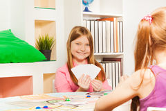 Happy girl playing cards with friends Royalty Free Stock Image