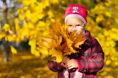 Happy girl playing with fallen leaves in autumn park royalty free stock image